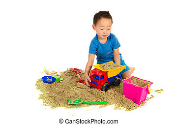 Chinese boy playing in the sand