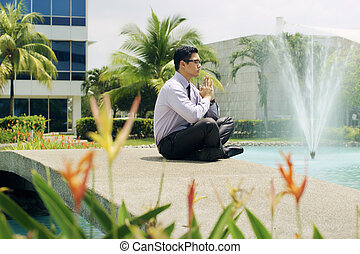 Chinese Business Man Meditate Yoga Outside Office Building