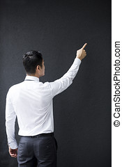 Chinese Business man pointing his finger at a wall.