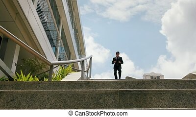 Chinese Businessman Going Downstairs Sliding On Rail For Joy...