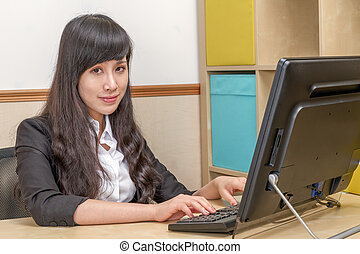 Chinese businesswoman at desk typing