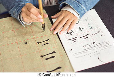 Chinese children learn to write Chinese characters,...