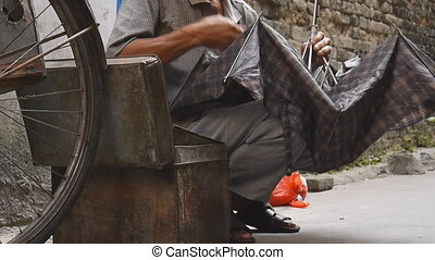 Chinese craftsman repairing umbrella