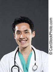 Chinese doctor wearing Green Scrubs & white coat.