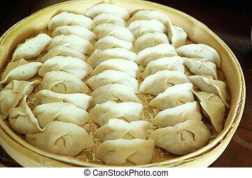 Chinese dumplings on the bamboo tray for steaming