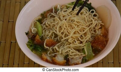 Chinese egg noodles topping crispy pork in soup picking by...
