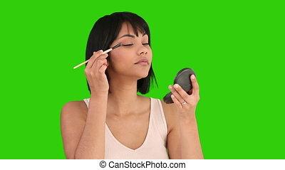 Chinese female putting on make-up