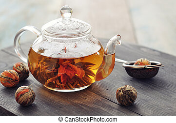 Chinese flowering tea in glass teapot on wooden background