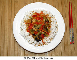 Veggies rice on a plate and red chopsticks