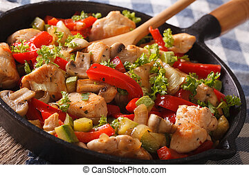 Chinese fried chicken with mushrooms and vegetables in a pan close-up. horizontal