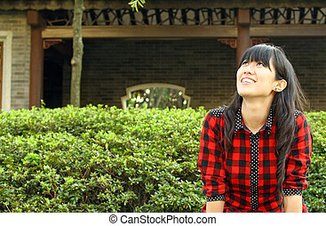 Chinese girl smiling in a garden