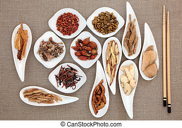 Chinese herbal medicine in white porcelain bowls with chopsticks over beige linen background.