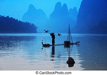 Chinese man fishing with cormorants birds in Yangshuo, ...