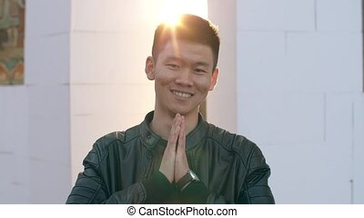 Chinese man greeting - Young smiling chinese man show...