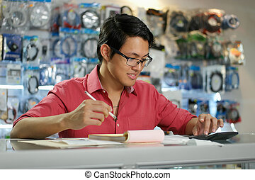 Chinese Man Working In Computer Shop Checking Bills And Invoices