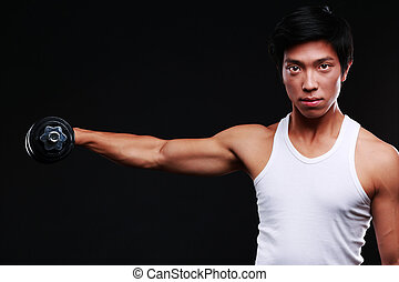 Chinese man working out with dumbbell on black background