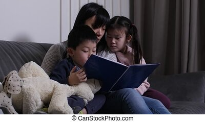Loving asian woman cuddling with little daughter and son while reading them book in living room. Interested children sitting on sofa in mom's hugs and listening to story during joint domestic leisure