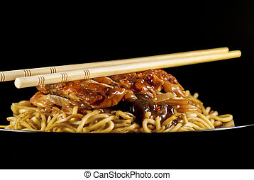 chinese noodle with chicken and vegetables on black ...