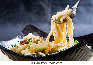 chinese noodles - a view of chinese noodles being held with...