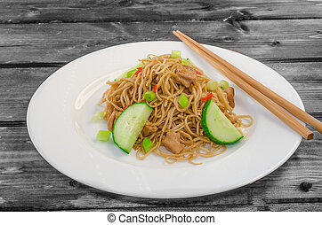 Chinese noodles with chicken on wood with chopsticks