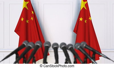 Chinese official press conference. Flags of China and...