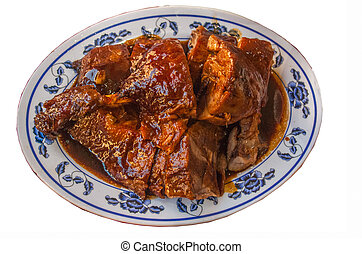 Chinese Roasted duck cut in piece and served on white dish topped with black gravy herbal sauce.