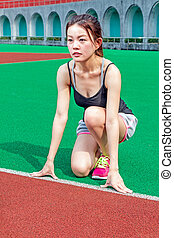 Chinese runner at starting position on racetrack