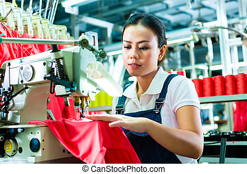 Seamstress or worker in factory sewing with industrial machine, she is very accurate