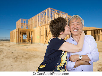 Chinese Senior Adult Couple Kissing In Front Of New House Framing at Construction Site.
