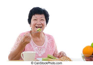 chinese senior female eating with isolated white background