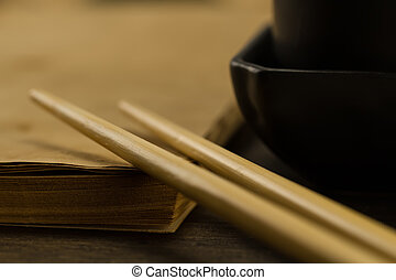 Chinese sticks on old blank open book on wooden background. Menu, recipe, mock up