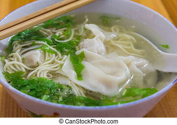 Chinese tasty wonton and noodle soup on white background.