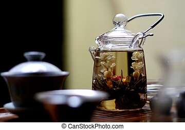 Flower tea in transparent glass teapot with chinese teacups