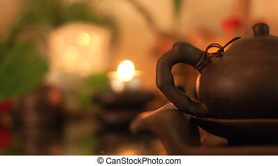Chinese tea pot on burning candles background. Tea kettle for traditional chinese ceremony. Asian culture and tradition