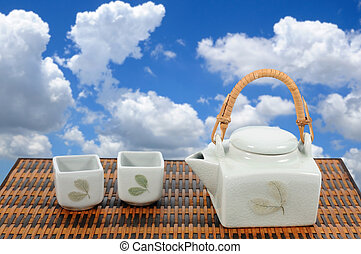 Chinese tea pot set on bamboo mat with blue sky.