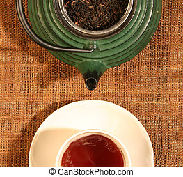 Chinese teapot with tea leaves and a cup of tea