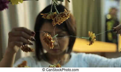 Chinese woman accurately hangs out floral decoration on wall.