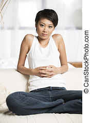 Chinese woman at home on the sofa.