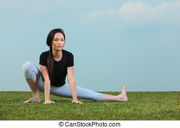 Chinese Woman in black t-shirt Performing yoga.