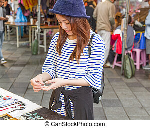 Chinese woman looking at jewelry at market