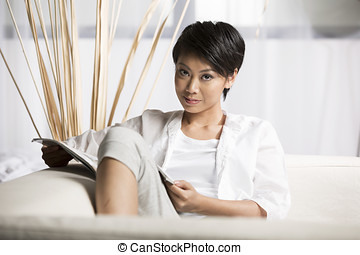 Chinese Woman reading a magazine at home