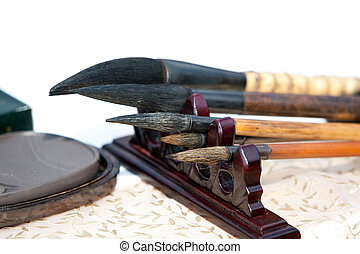 Chinese writing brushes and inkstone on the table, these is two tools of Four Treasures of the Study in Chinese whick is an expression used to denote the brush, ink, paper and ink stone used in Chinese and other East Asian calligraphic traditions.