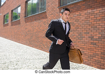 Chinese young businessman running in a city street