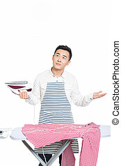 chinese young man ironing his clothes