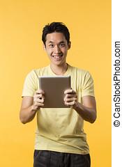chinesisches , mann, gebrauchend, a, tablette pc, vor, gelber , hintergrund.
