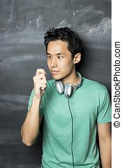 chinesisches , mann, tragen, kopfhörer, vor, a, blackboard.