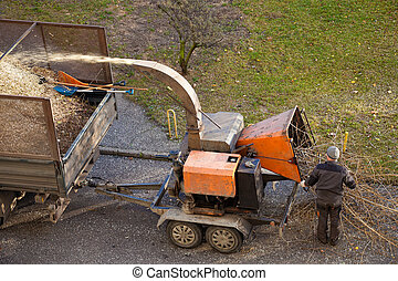 Chipper machine - Tree branches are placed in the intake...