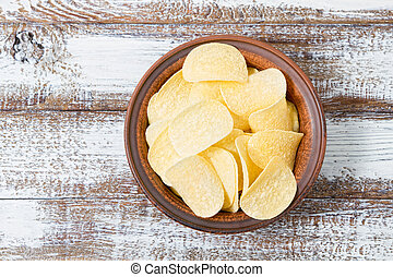 chips in a plate top view, wooden table, food
