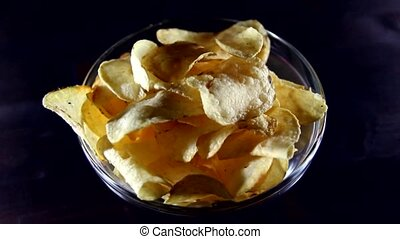 Chips on bowl on a wooden table in rotation