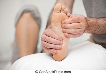 Chiropodist palpating the sole of the foot of a patient in...